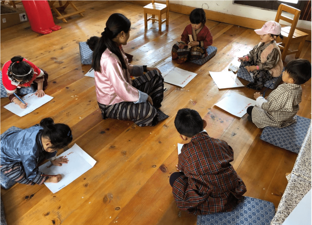 Young Bhutanese children in national dress huddle over paper making books with their teacher watching on at a Bhutanese early childhood demonstration school