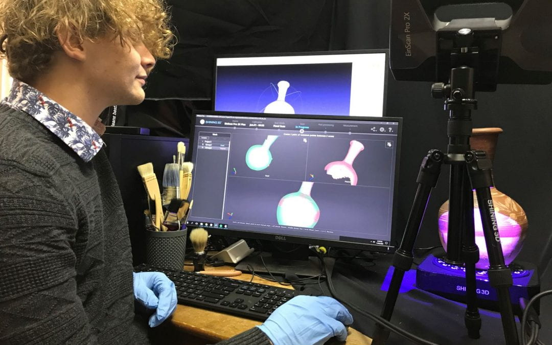UNE history graduate Jackson Shoobert wears gloves in a computer lab environment as he prepares to upload images of an ancient vase artefact onto an online platform seen on a computer screen.