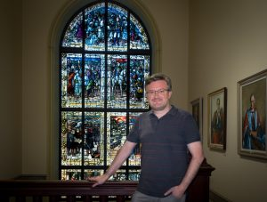 Dr Richard Scully before Booloominbah's stained-glass window celebrating the Victorian-era empire-building exploits of General Charles Gordon.
