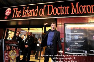 Matthew Reilly standing outside the venue of the hit musical 'The Island of Dr Moron.'