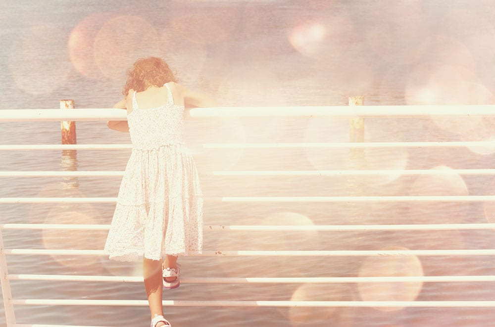 Young girl leaning over a railing on a pier, looking at the sea. Pink and peachy hues.