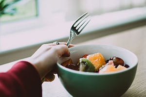 Bowl of healthy food, with a hand holding a fork.