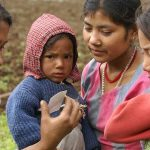 Three Nepalese women with a child, looking at a photograph, in a rural setting.