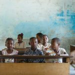 Malagasy school children sitting on desks in a basic room with rough plaster on the walls.