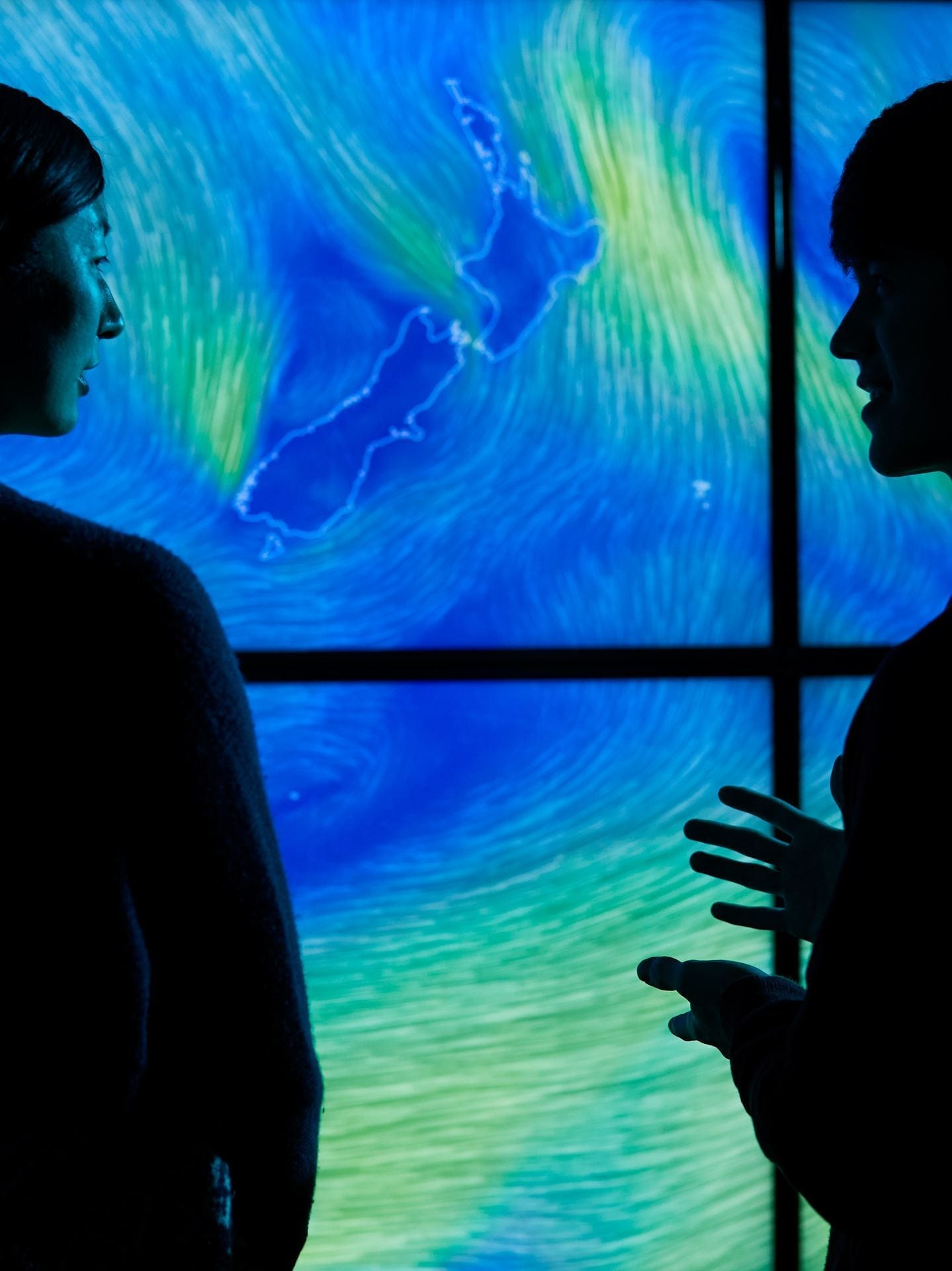 Two students discussing weather patterns displayed on a large screen