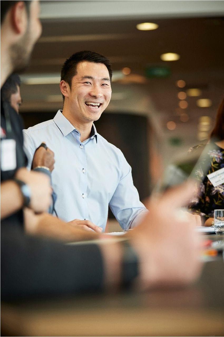 Daniel looking cheerful at a meeting
