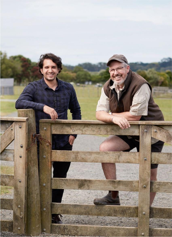 Matheus and Paul leaning against a farm gate