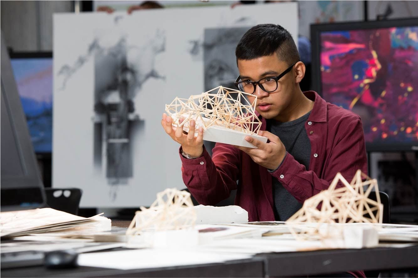 Student examining his detailed model made from skewers