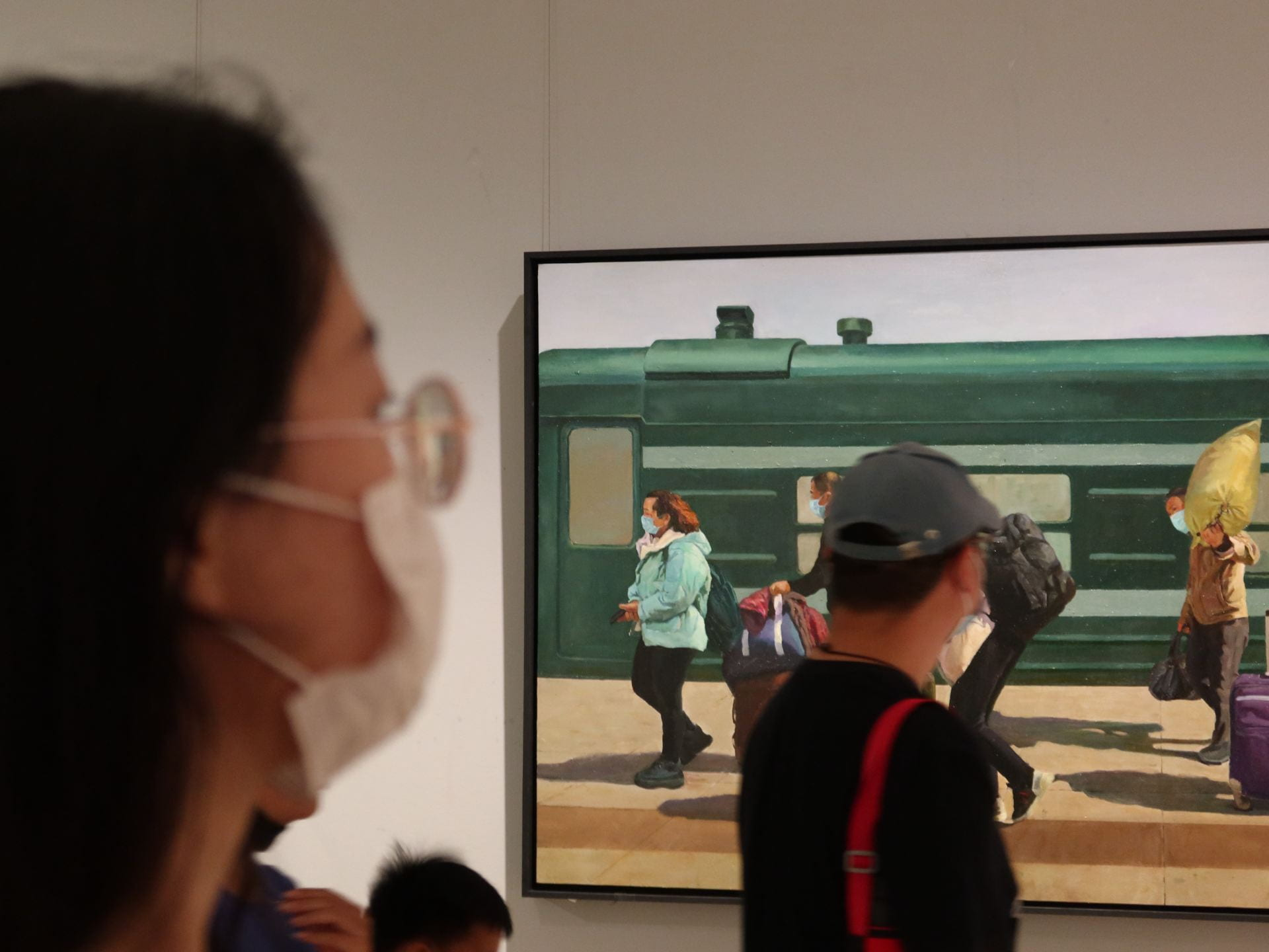 Person wearing a mask, looking at someone else who is looking at a painting of people getting off a train, all wearing masks