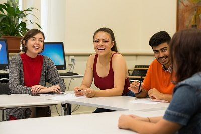 Smiling students seated around table