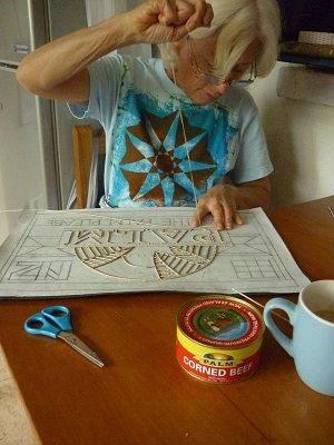 Artist Dame Robin White stitching on ngatu cloth