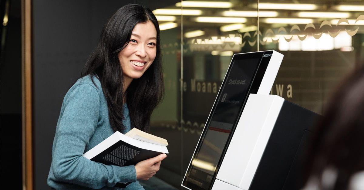 girl checking out books through self-service machine