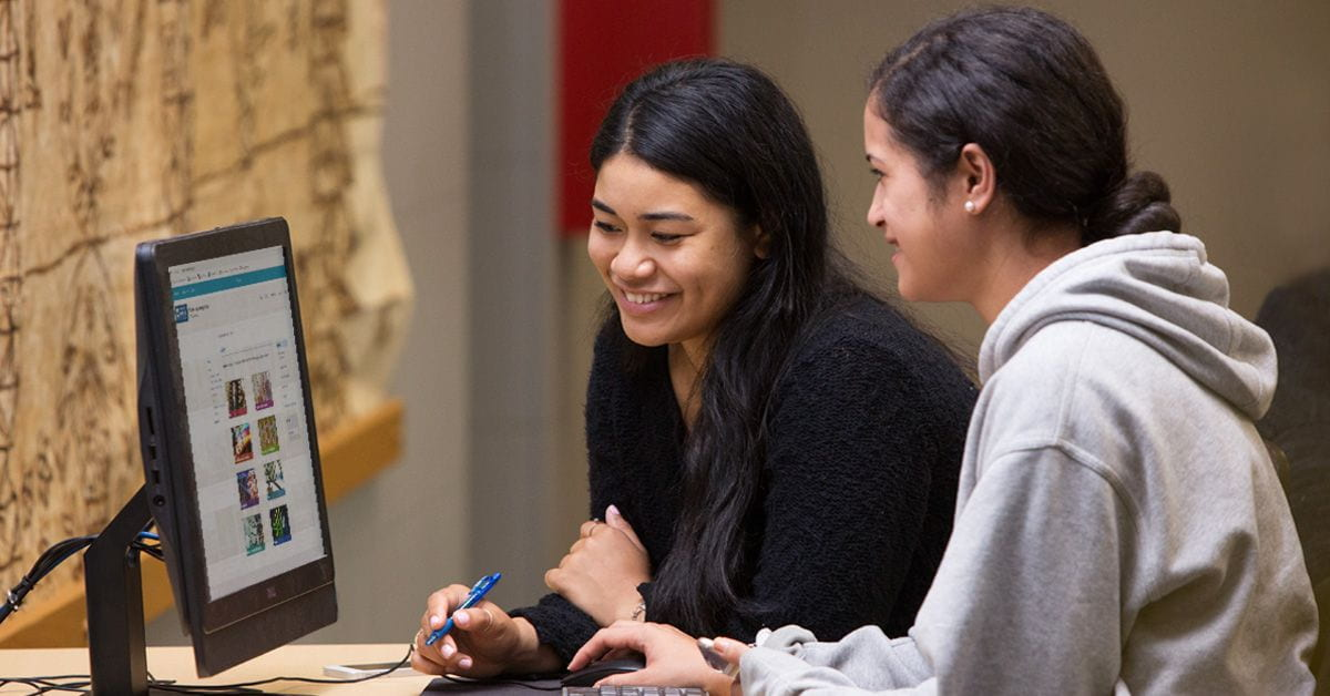 Two students look at the library website on a computer screen