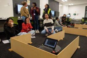 Teenage girls laughing as a pioneer robot navigates through a wooden maze