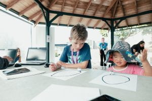 Two children watching line drawing robots on a table in front of them