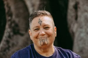 Photo of Dr. Huhana Hickey, an indigenous Ngāti Tāhinga, Whakatōhea Māori woman with light brown skin and cropped brown hair. She carries moko kauae on her forehead and chin, and smiles into the camera. She wears a dark blue t-shirt.