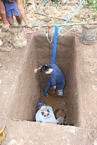 Alex and Ethan pumping out water of a really deep hole. There is the sand layer at the bottom of all that muck.
