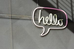 "Neon sign saying ""hello"" in a quote bubble"