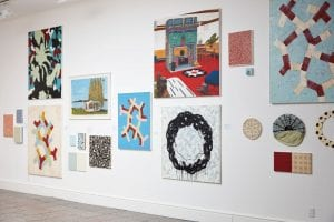 An image of one wall of the exhibition. A white wall is covered in numerous paintings in different mediums, and colours, some look figurative, some look abstract. The works are hung in a salon fashion, some high up and some below.
