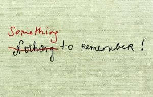 Promotional image for Something to Remember. 'Nothing to remember' is written in black scrawling hand-writing across a hessian background, mimicking the title of an artist book by Louise Bourgeois. 'Nothing' is crossed out in red and replaced with 'Something' written above it in red.