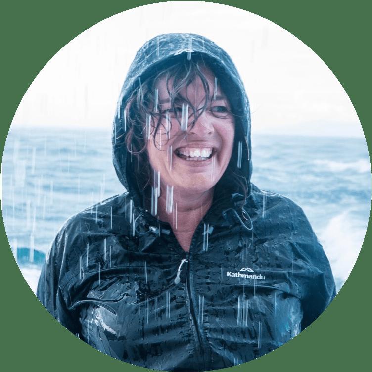 Juliet smiling wearing a rainjacket in the rain in front of the ocean