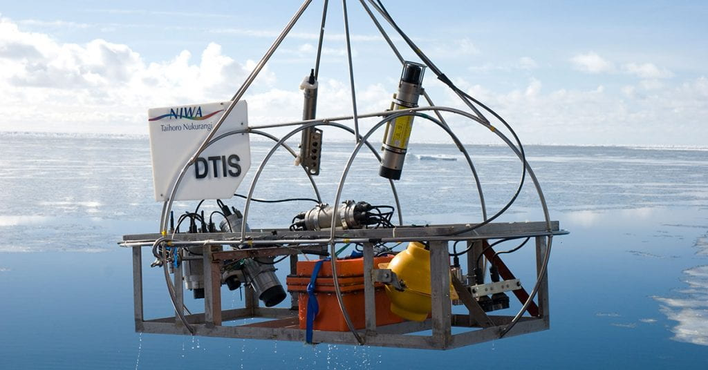 DTIS being winched out of the water in Antarctica. The sky and sea are blue, with ice floes and fluffy clouds visible in the background