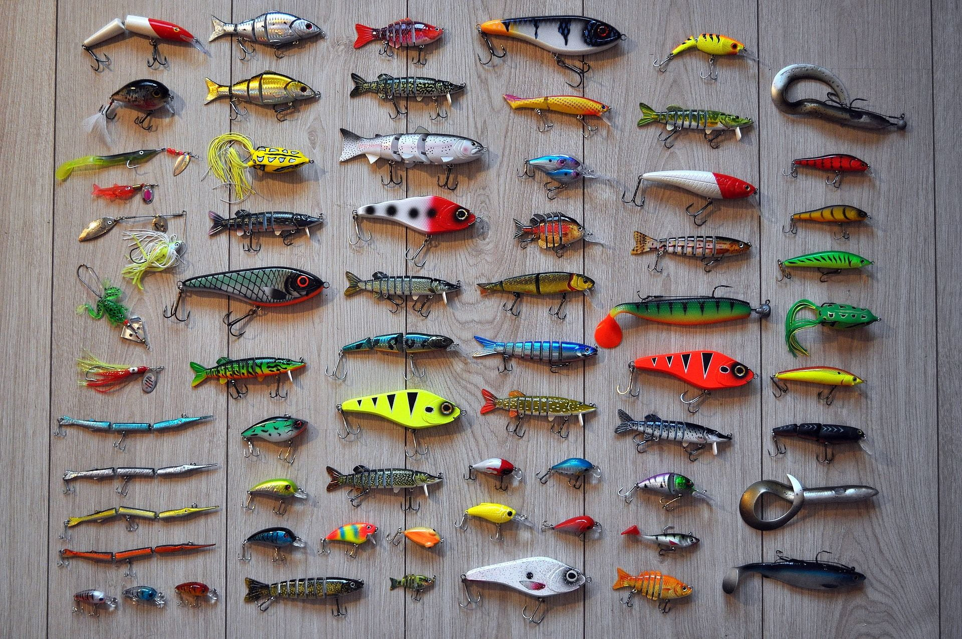 A large variety of brightly coloured jigs laid flat on a table