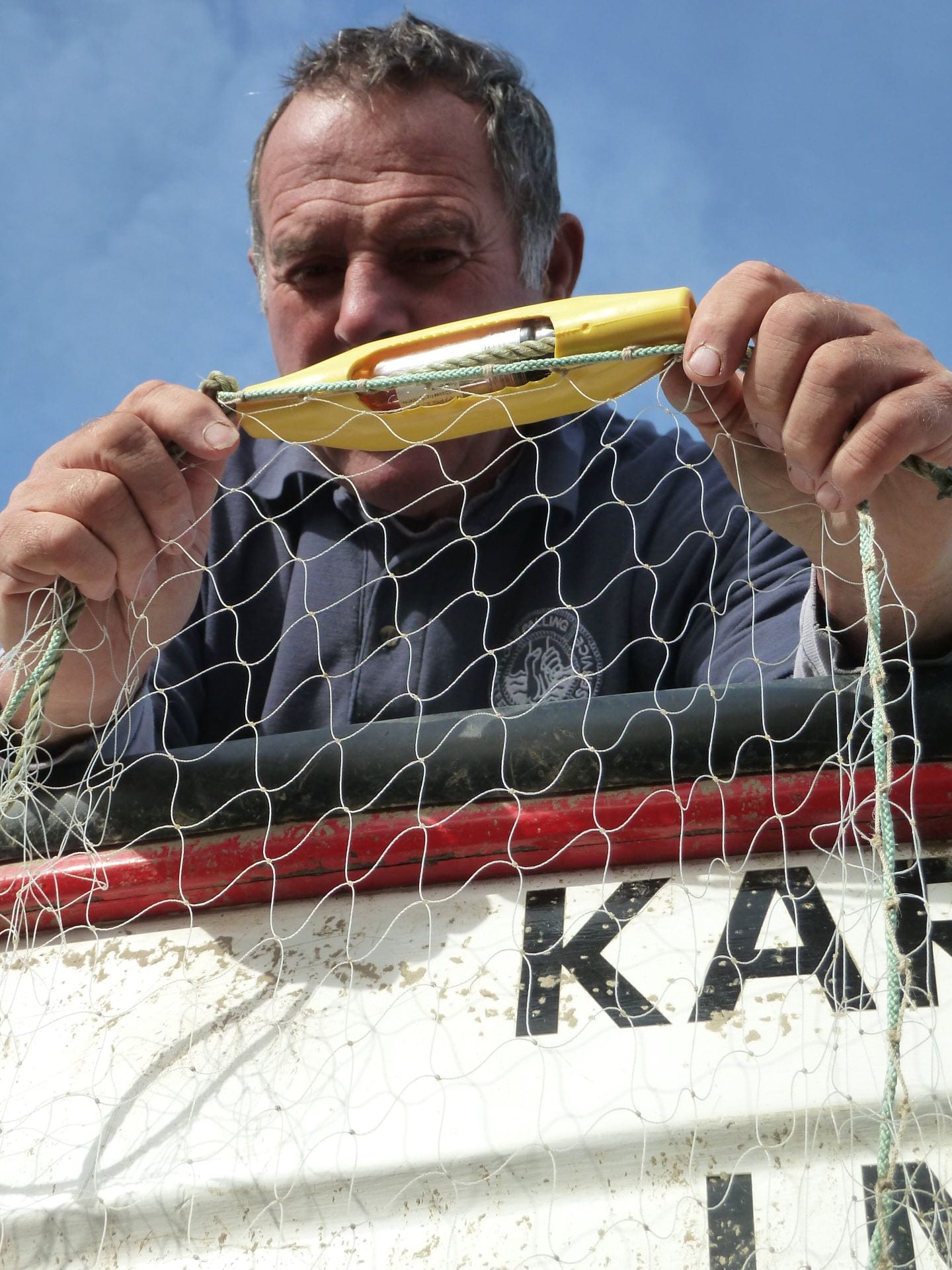 An old man holding up a net with a banana-shaped plastic attachment on the edge