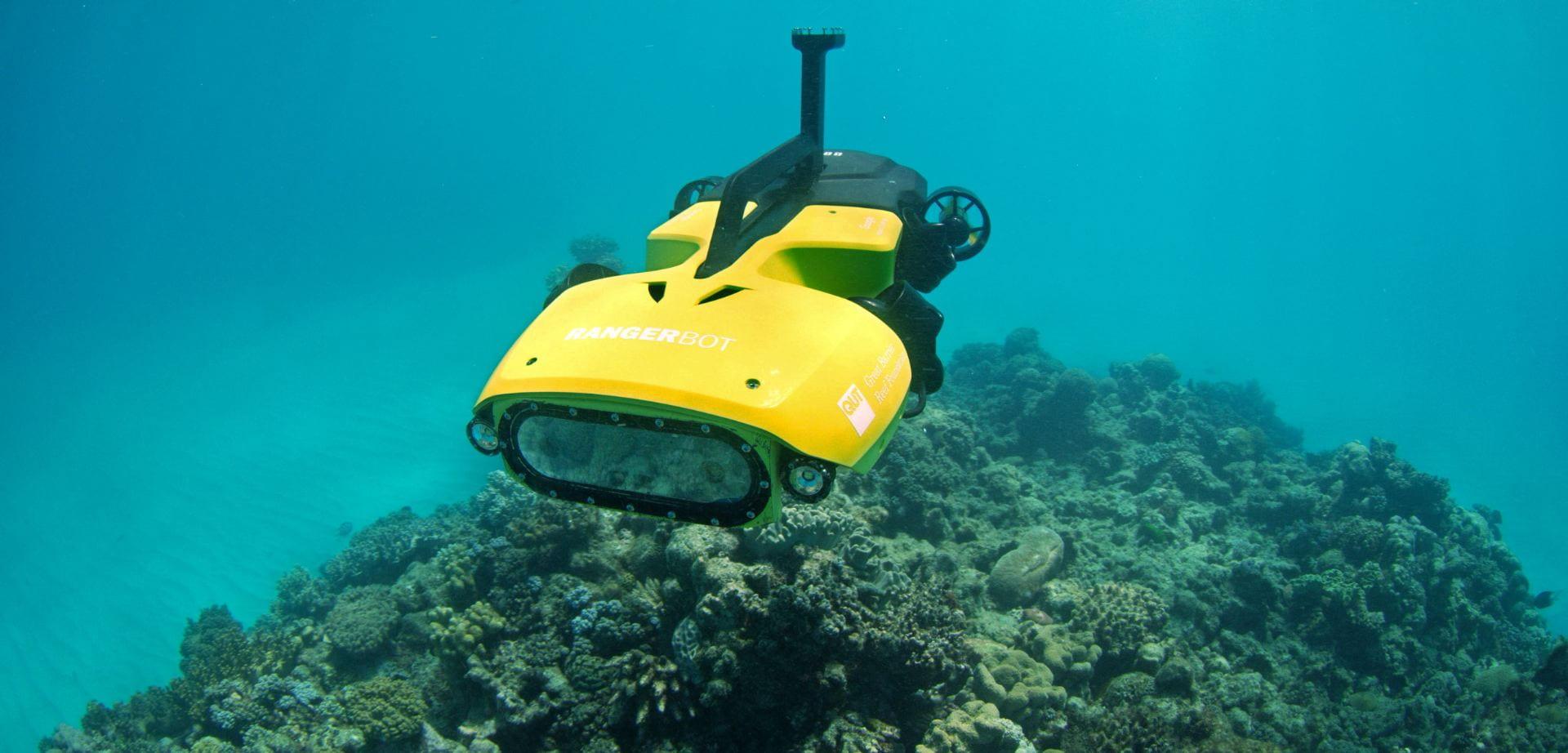 A yellow submersible autonomous vehicle navigates above a coral reef.