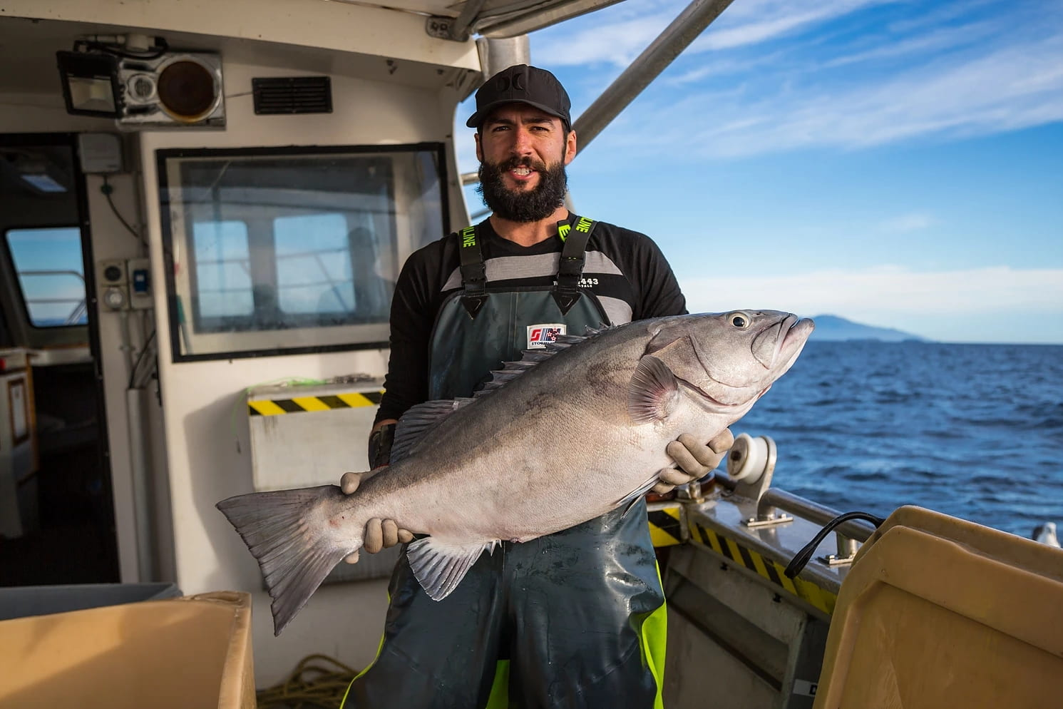 A smiling man with a beard and a cap stands on the deck of a fishing vessel, holding a large silver-grey fish