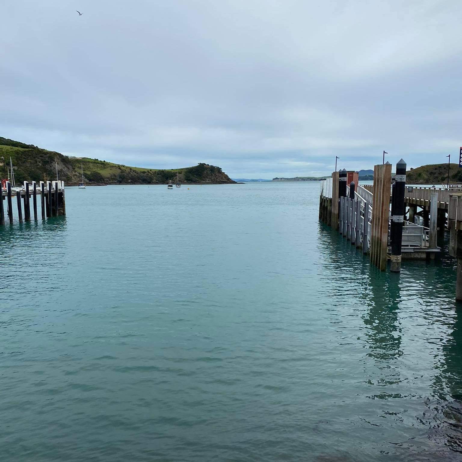 Still harbour water between two jetties beneath a moody grey sky