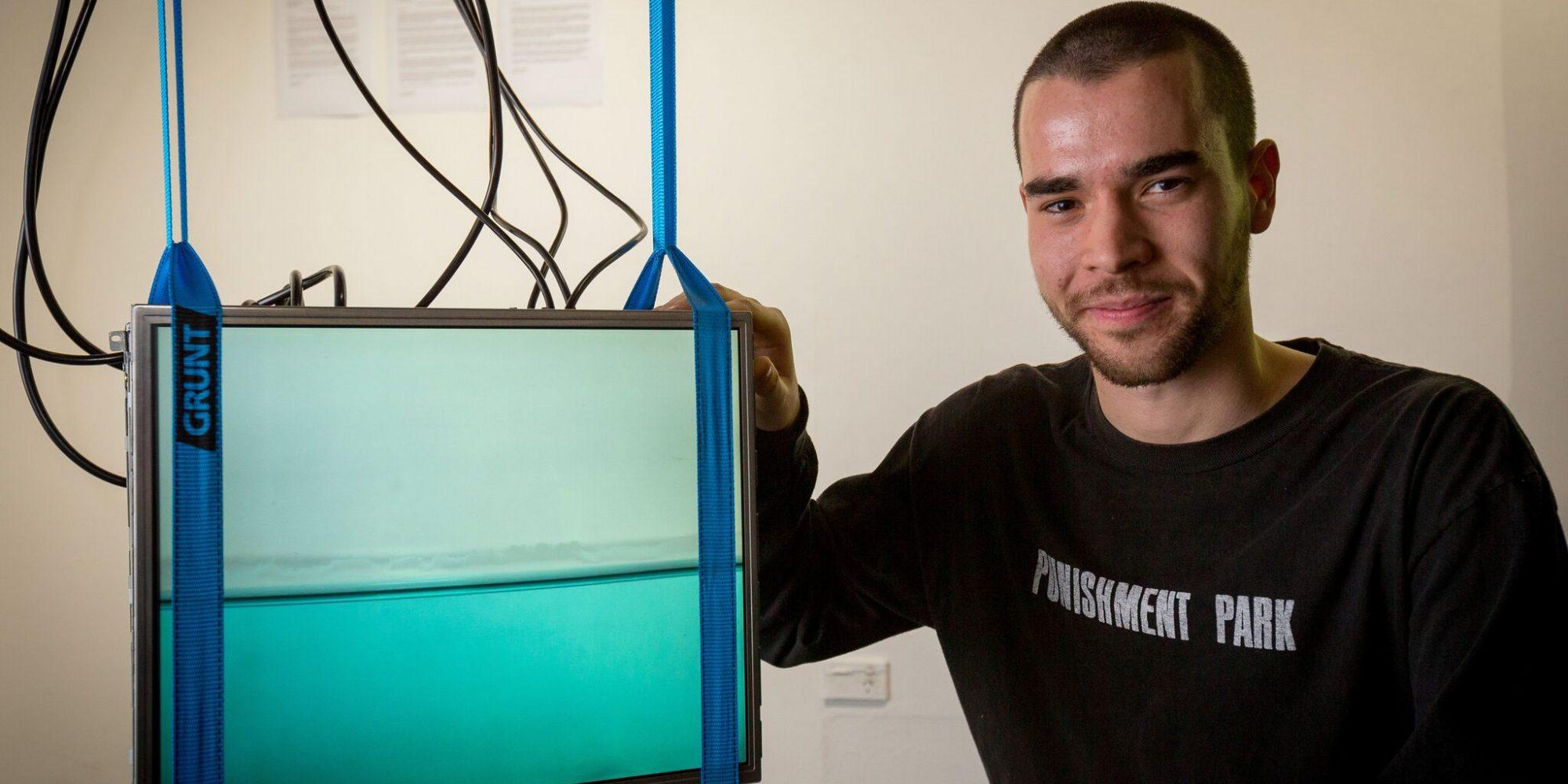 Trent Crawford with his video installation work Liquidity. Photo: Sav Schulman.