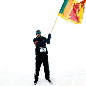 Hassan Esufally on the snow, waving a flag.