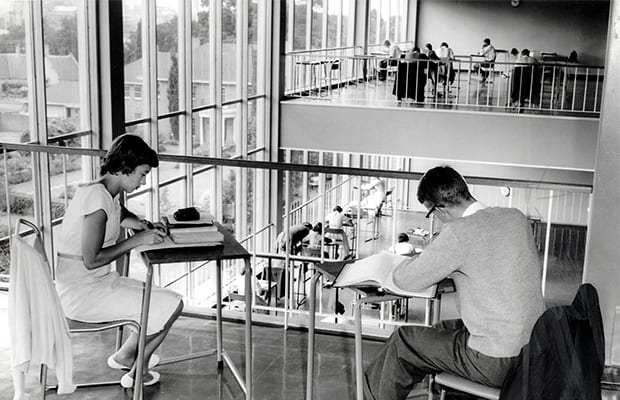 Black and white image of students sitting in the library.