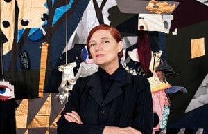 Professor Sally Smart standing in front of a textile artwork.