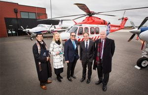 A group of people standing in front of a medical helicopter.