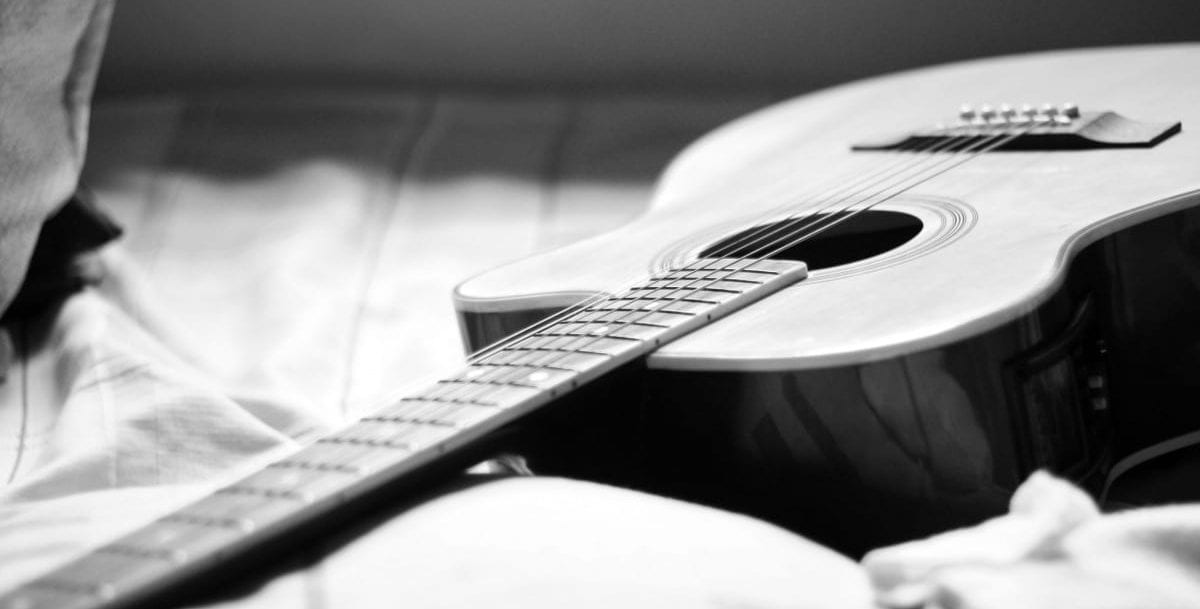 Guitar lying on a bed