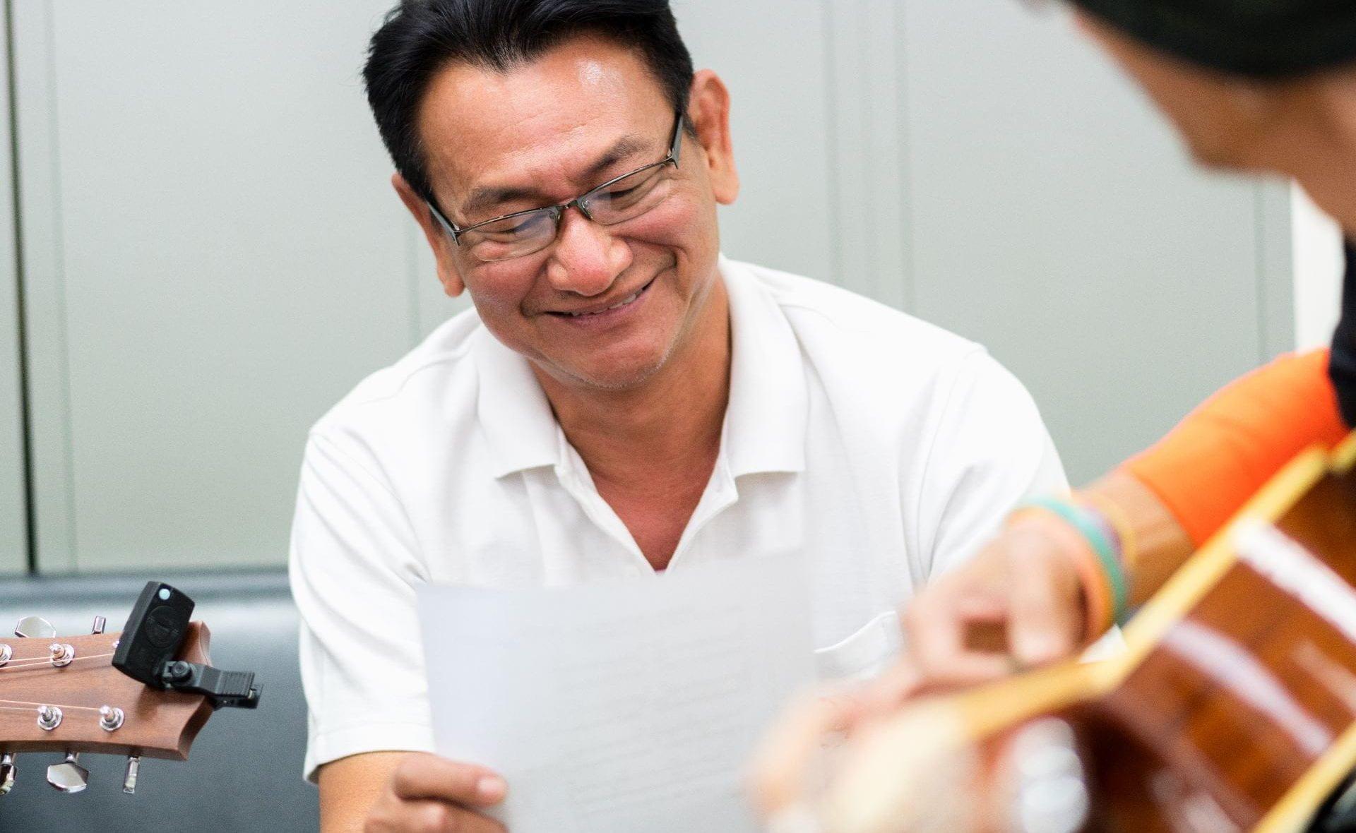 Man singing and smiling to guitar music