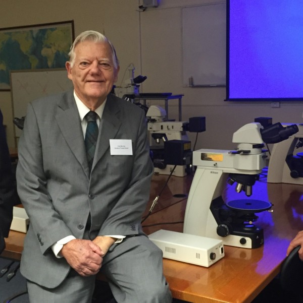 Goodeve Trustee, Tony Munday, next to one of the donated microscopes