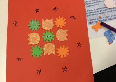 Symmetrical pattern involving orange and green, stars and flowers