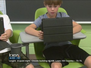 Image of child with an ipad from the KXAN Report on the KXAN site
