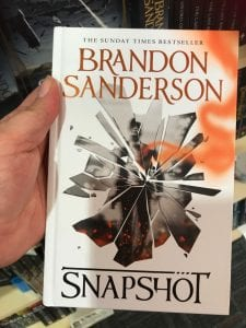 My hand holding a copy of Snapshot by Brandon Sanderson