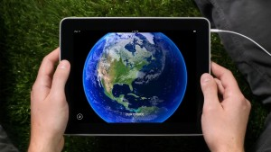 hand holding ipad with picture of globe